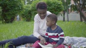 可爱的非裔美国人的妇女坐毯子在有她的小儿子的公园 尝试的年轻母亲 股票录像