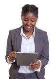 可爱的非洲女实业家与片剂计算机一起使用 库存图片