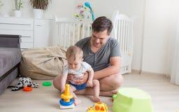 可爱的10个月使用与在地板上的父亲的男婴在卧室 库存图片