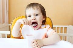 可爱的18个月吃youghourt的婴孩 图库摄影