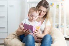 可爱的10个月坐母亲膝部和听童话的小孩男孩 库存照片