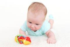 可爱的2个月女婴使用与吵闹声 免版税库存照片