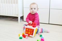 可爱的10个月女婴如此演奏戏剧教育房子形状 免版税图库摄影