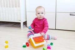 可爱的10个月女婴演奏房子形状整理者 免版税库存图片