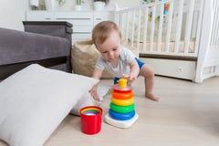 可爱的10个月小孩男孩坐地板和修造的玩具塔 库存图片