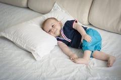 可爱的10个月被定调子的照片在床上的bbay男孩 免版税库存照片