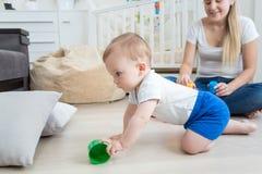 可爱的10个月婴孩爬行和获得在地板上的乐趣在 免版税库存图片