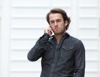 可爱的年轻人谈话在手机 免版税库存图片