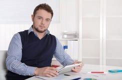 可爱的年轻企业家与数字式片剂一起使用。 库存图片