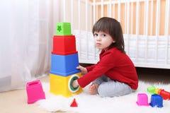 可爱的2年在家使用与教育玩具的小孩 免版税库存图片