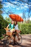 可爱的年轻夫妇骑马和亲吻在有红色d的自行车 库存照片