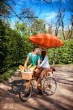 可爱的年轻夫妇骑马和亲吻在有红色d的自行车 免版税库存图片