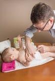 可爱的婴孩父亲改变的尿布  免版税库存图片
