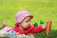 可爱的婴孩要种植在地面的红萝卜 库存图片