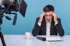 可爱的年轻新闻广播员有痛苦在他的头 库存照片