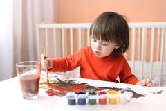 可爱的2年有刷子和树胶水彩画颜料油漆的男孩在家 免版税图库摄影