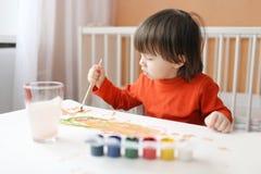 可爱的2年有刷子和树胶水彩画颜料油漆的男孩 库存照片