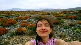 可爱的年轻深色的女孩,单独旅行和做在智能手机微笑的嘴的一selfie 免版税库存照片