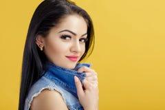 可爱的年轻深色的妇女画象牛仔布背心的在黄色背景 免版税库存照片