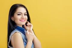 可爱的年轻深色的妇女画象牛仔布背心的在黄色背景 免版税图库摄影