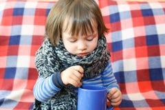 可爱的2年温暖的羊毛围巾和茶的不适的小孩 免版税库存图片