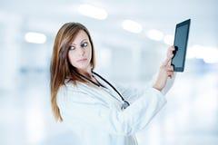可爱的医生与数字式片剂一起使用 免版税图库摄影
