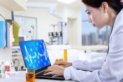 可爱的医生与膝上型计算机一起使用在实验室 库存图片
