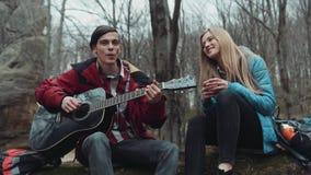 可爱的年轻男孩弹吉他给喝茶的他可爱的白肤金发的欧洲女朋友,他们笑 股票录像