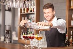 可爱的年轻男服务员在客栈做饮料 免版税库存图片