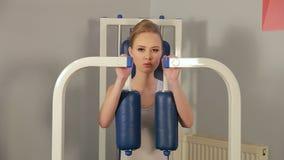 可爱的年轻白肤金发的女孩参与胸口和胳膊的肌肉的一台模拟器健身房 影视素材