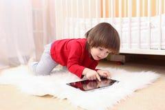 可爱的2年红色衬衣的男孩有片剂计算机的在家 免版税图库摄影