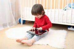 可爱的2年红色衬衣的男孩有片剂计算机的 库存照片