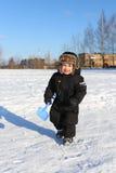 可爱的2年走与铁锹的小孩在冬天 免版税库存照片