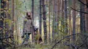 年轻可爱的-走在秋天森林的妇女和她的宠物-德国牧羊犬 免版税库存图片