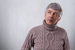 可爱的年长人画象有有的皱痕的查找佩带的毛线衣的周道和沉思表示 孤独的参议员 免版税库存图片