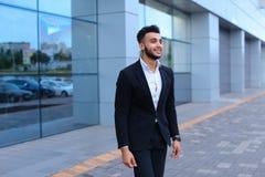 可爱的年轻阿拉伯人今后在backgrou站立并且看 免版税库存照片