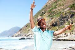 可爱的年轻非洲人获得乐趣在海滩 图库摄影
