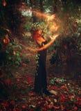 可爱的年轻redhair夫人巫术师在森林里召唤 免版税库存图片
