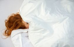 可爱,年轻,性感,红发妇女,面对几乎完全地盖由枕头,一只眼睛偷看  免版税库存图片