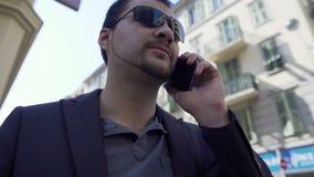 可疑人谈话在电话,匪徒小组的成员在城市街道的 股票录像