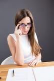 可疑看在玻璃的女实业家 图库摄影