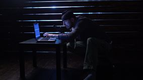 可笑的滑稽的黑客做与一台膝上型计算机和一杆枪的一次网络攻击在他的手上 股票视频