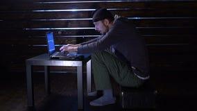可笑的滑稽的黑客做与一台膝上型计算机和一杆枪的一次网络攻击在他的手上 股票录像
