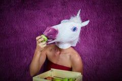 可笑面具的怪异的少妇在紫色背景站立 免版税库存照片