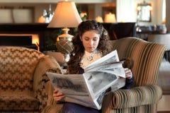 可结婚女孩在一把古板的扶手椅子坐,穿戴在葡萄酒天鹅绒紫色礼服并且读报纸 库存图片