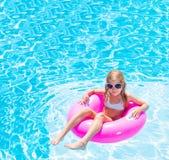 可膨胀的圆环的女孩在游泳池 免版税库存照片