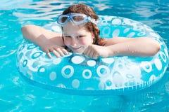 可膨胀的圈子的女孩在蓝色露天水池 图库摄影