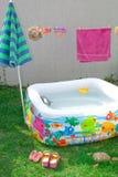 可膨胀的水池在庭院里,有伞的 免版税库存照片
