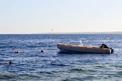 可膨胀的灰色小船、一个汽船有一个马达的在盐蓝色海以浮体为背景和遥远的山 库存照片