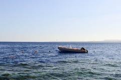 可膨胀的灰色小船,有一个引擎的一个汽船在反对遥远的山背景的盐蓝色海  免版税库存图片